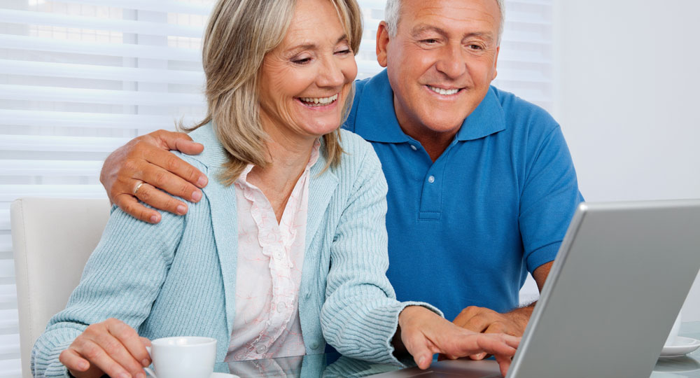 happy older couple looking at a computer