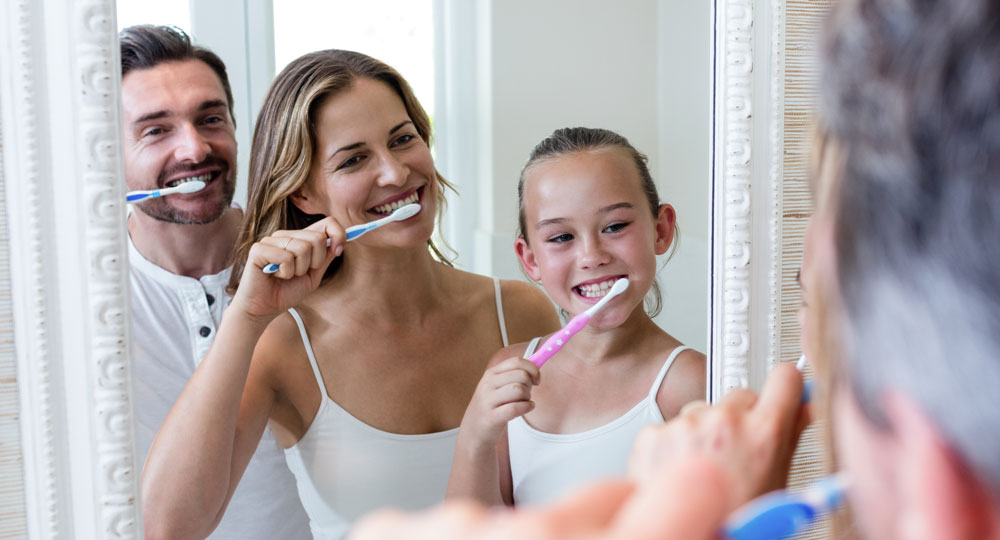 Parents and daughter brushing their teeth in the bathroom.